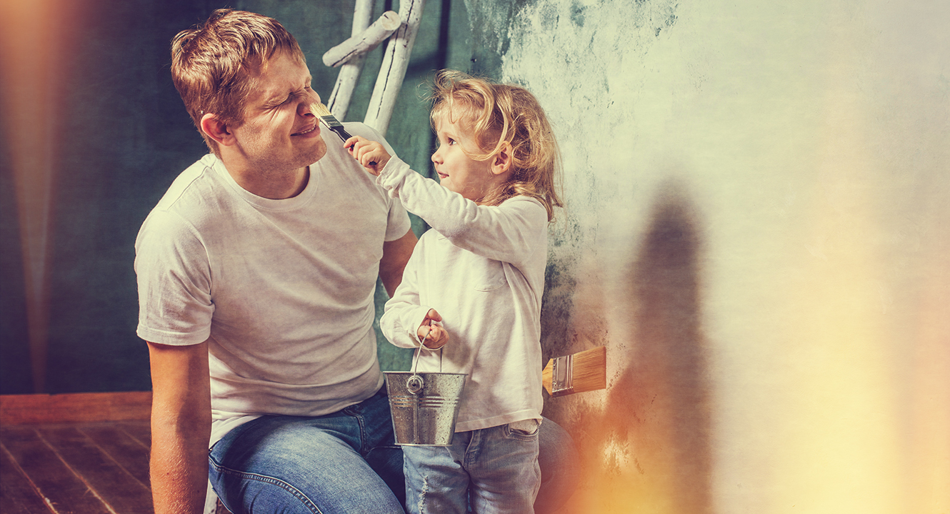 father and young daughter painting their house