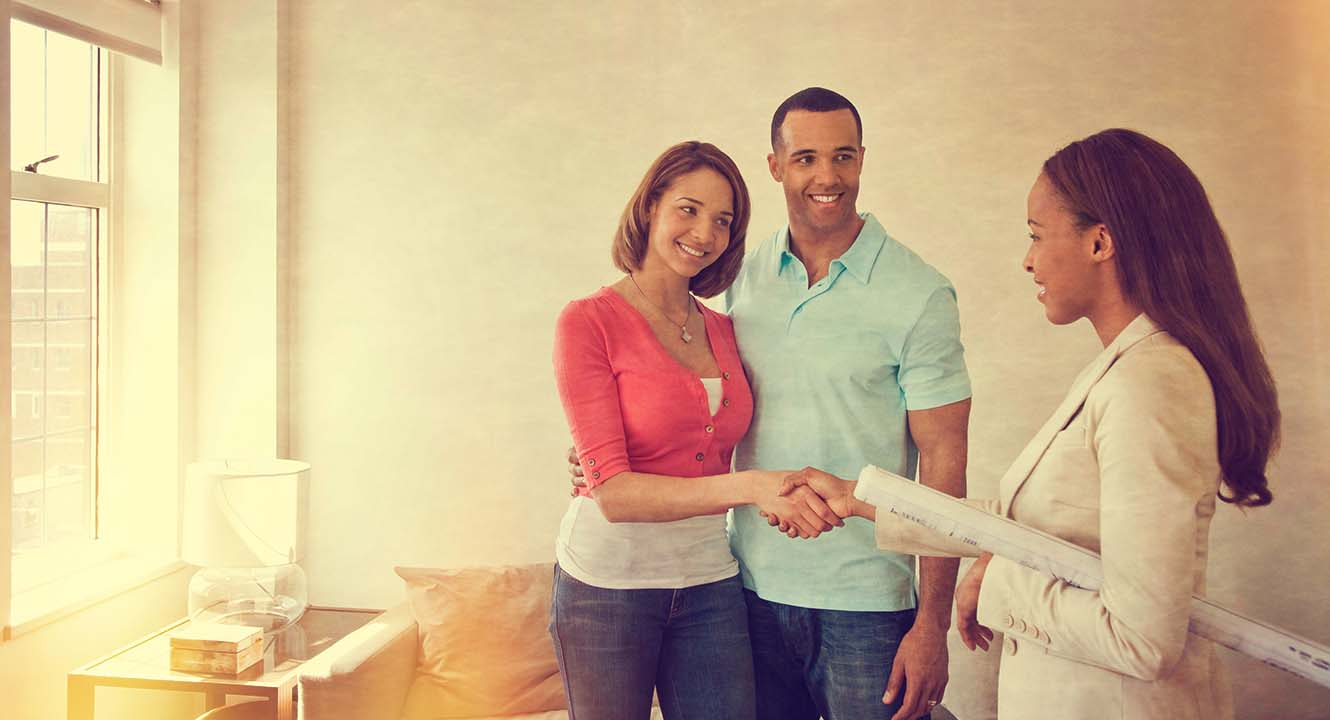 young couple shaking hands with their realtor
