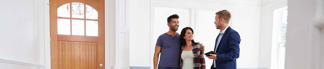 young couple viewing a house with a realtor