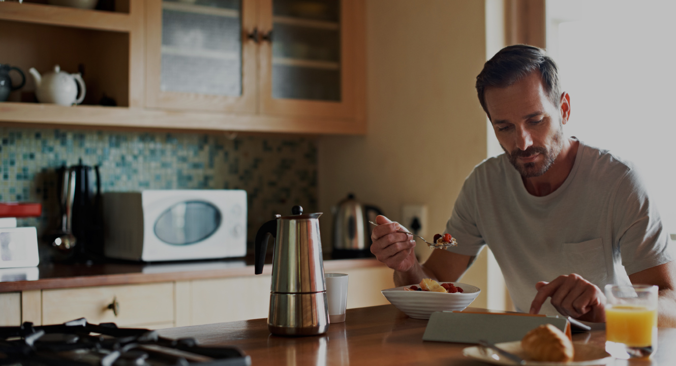 man eating breakfast using tablet