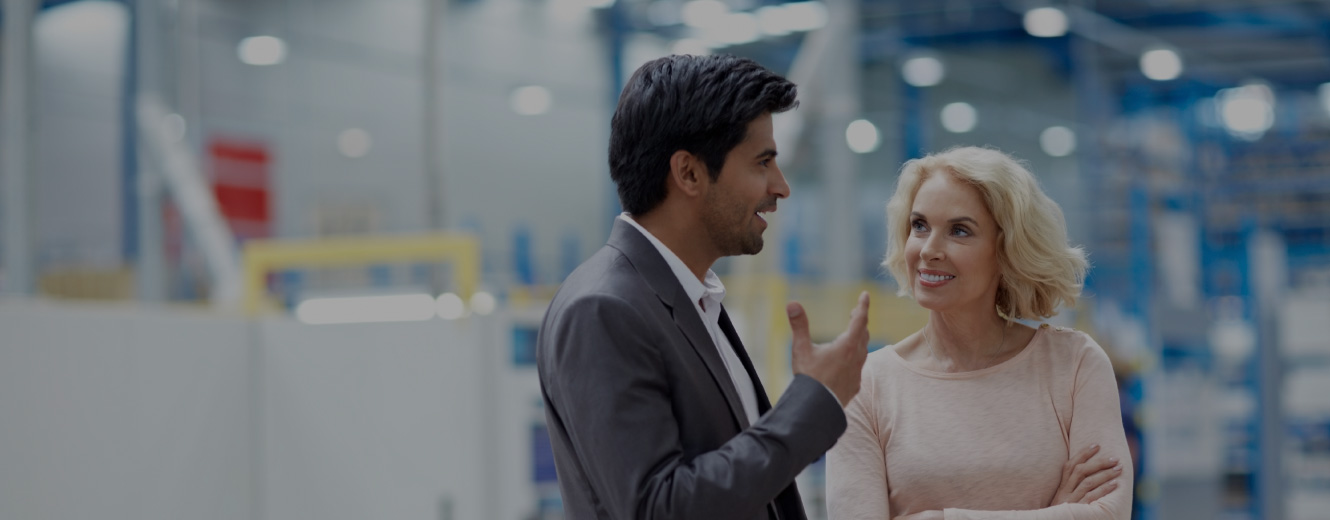 man and woman talking in a warehouse