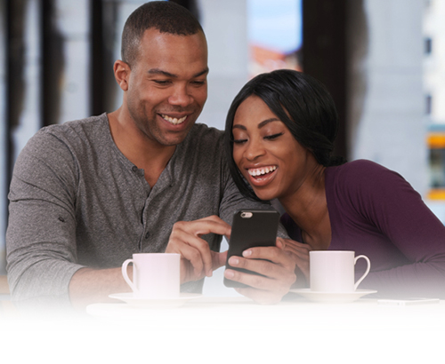 young couple laughing and using their smartphone at a cafe