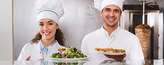two chefs holding up meals