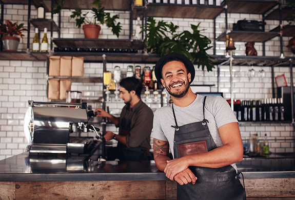 coffee shop owner standing at the counter smiling