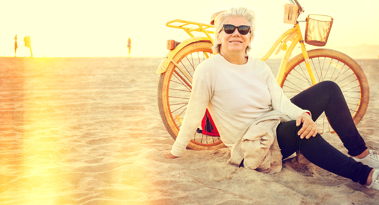 a woman in her 60's sitting on the beach next to her bike