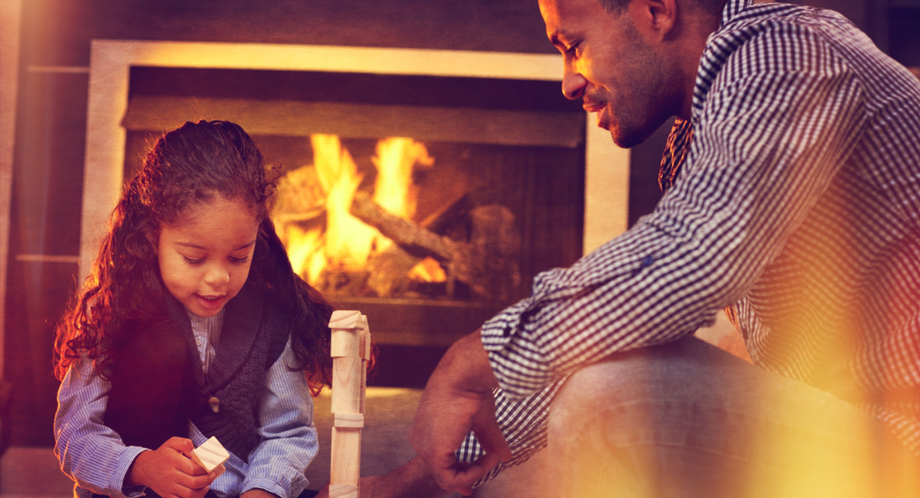 father and daughter building blocks at home in front of the fireplace