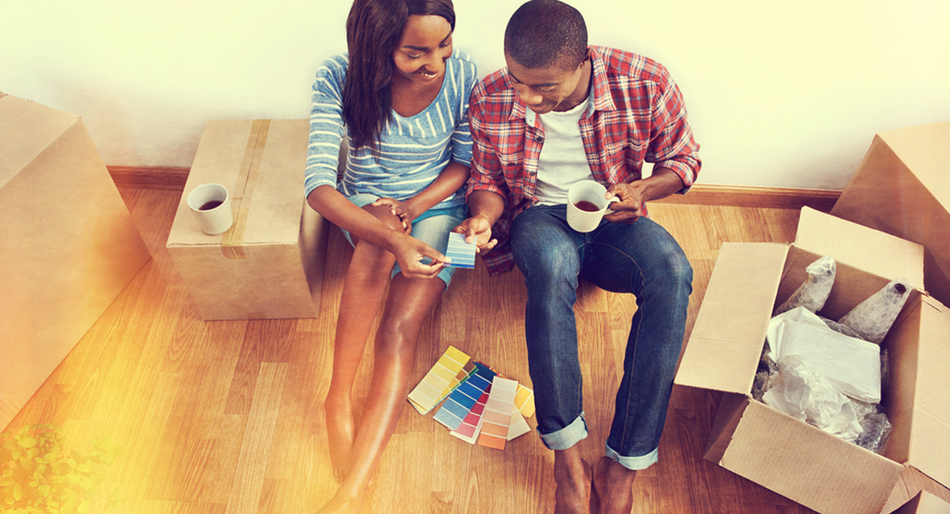 young couple sitting on the floor of their new home picking out paint colors
