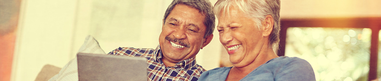 older couple sitting in their home smiling