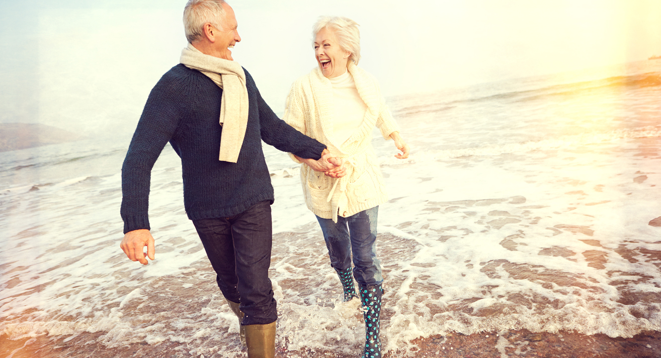elderly couple running on the beach hand in hand