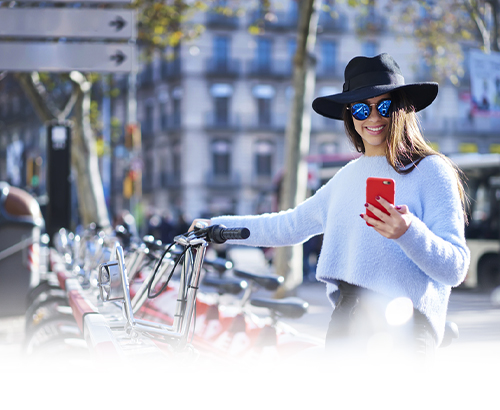 young woman in the city at a bike share on her smartphone