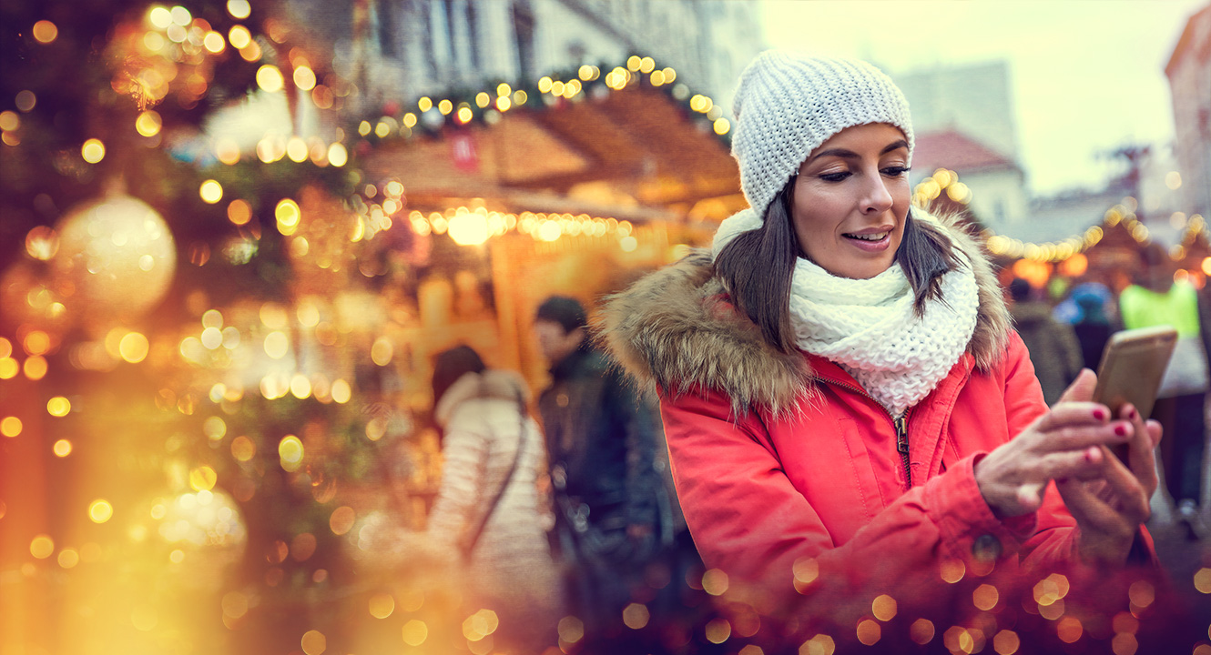 Woman wearing winter jacket standing outside looking at mobile phone