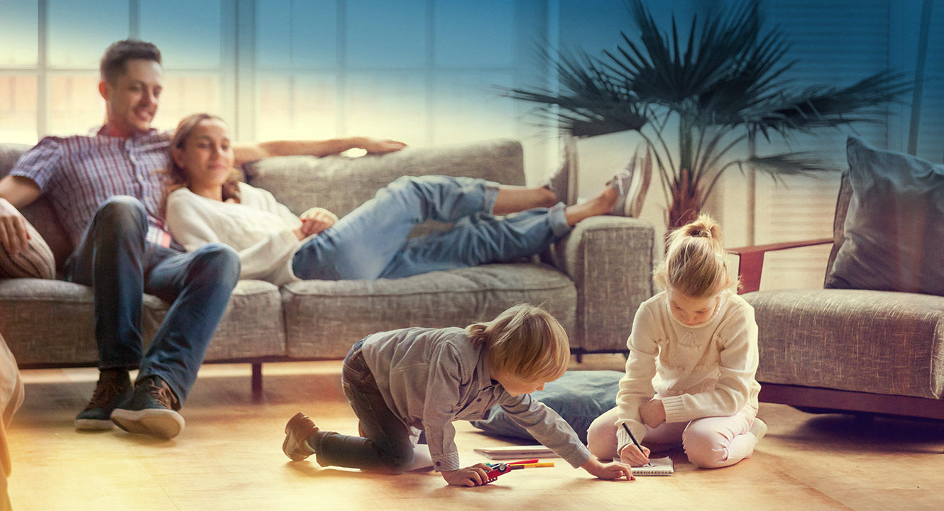 Parents on the couch watching their children play together on the floor.