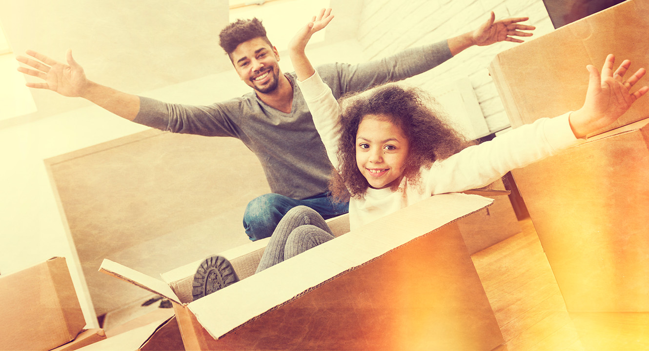 a young dad with his young daughter playing in moving boxes